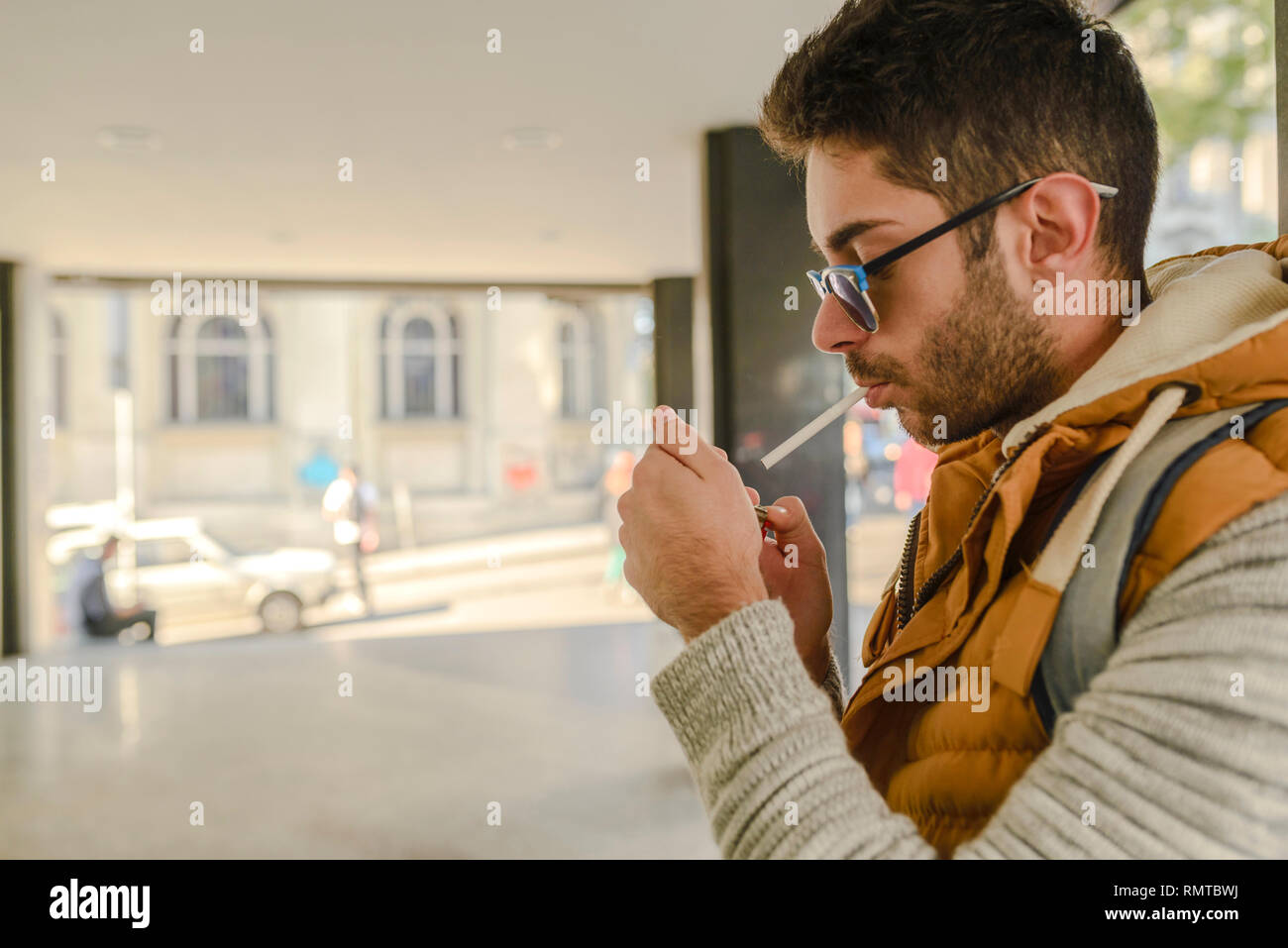 Young handsome hipster with orange jacket and sunglasses enjoying a cigarette in the street. - Stock Image