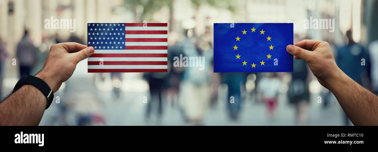 Two hands holding different flags, EU vs USA on politics arena over crowded street background. Future strategy, relations between countries. Cooperati - Stock Image