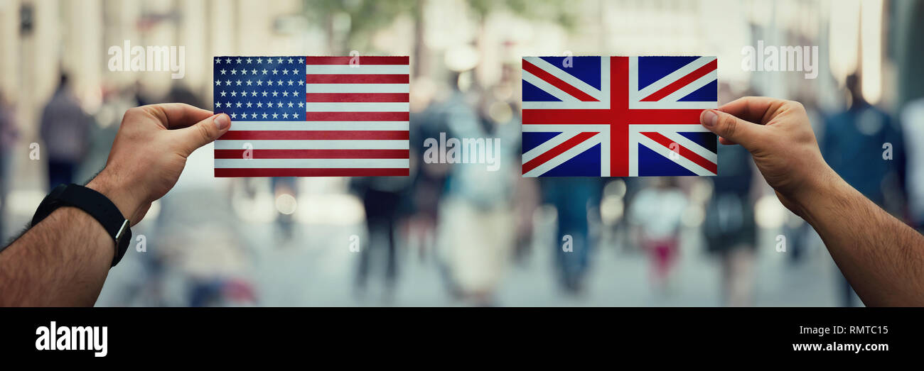 Two hands holding different flags, UK vs USA on politics arena over crowded street background. Future strategy, relations between countries. Cooperati - Stock Image