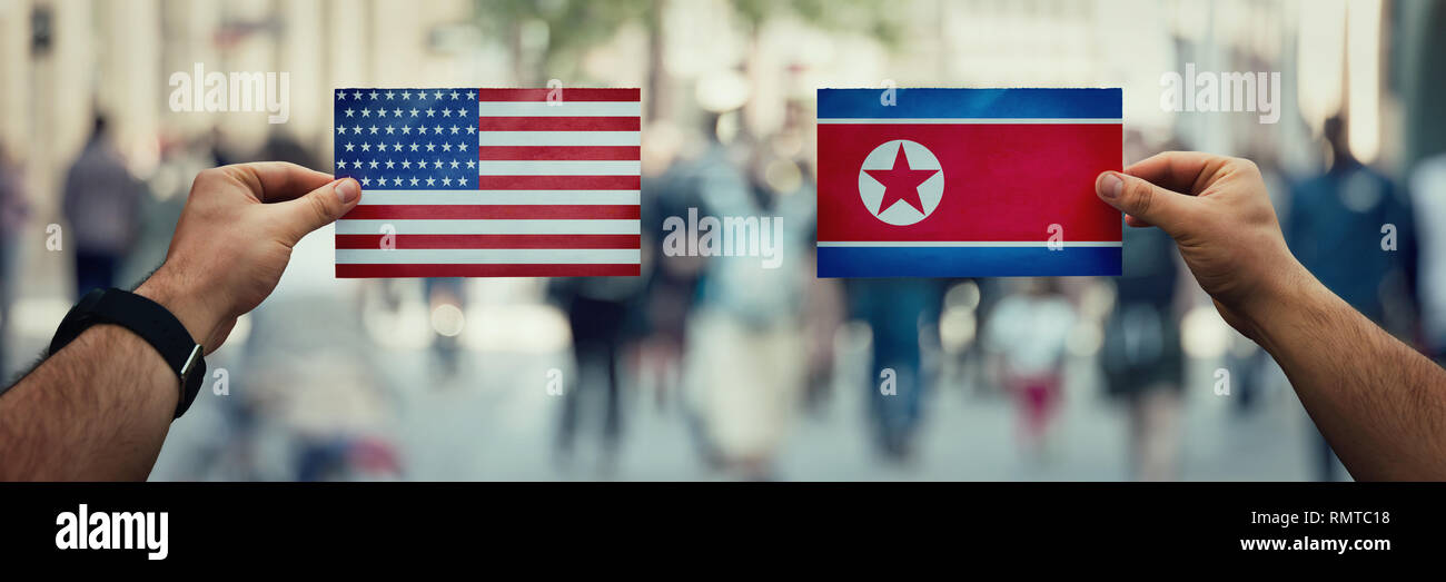 Two hands holding different flags, USA vs North Korea Republic on politics arena over crowded street background. Future strategy, relations between co - Stock Image