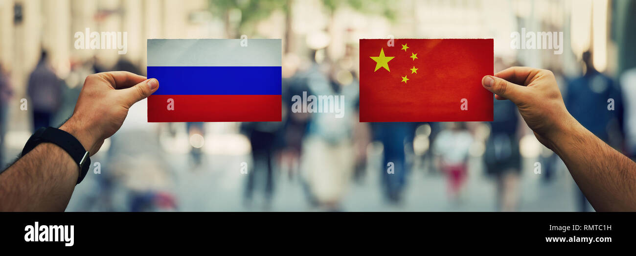 Two hands holding different flags, China vs Russian Federation on politics arena over crowded street background. Future strategy, relations between co - Stock Image