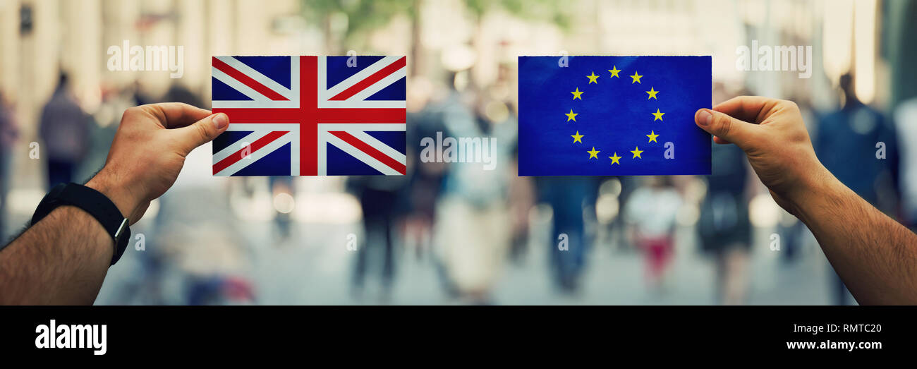 Two hands holding different flags, EU vs UK on politics arena over crowded street background. Future strategy, relations between countries after brexi - Stock Image