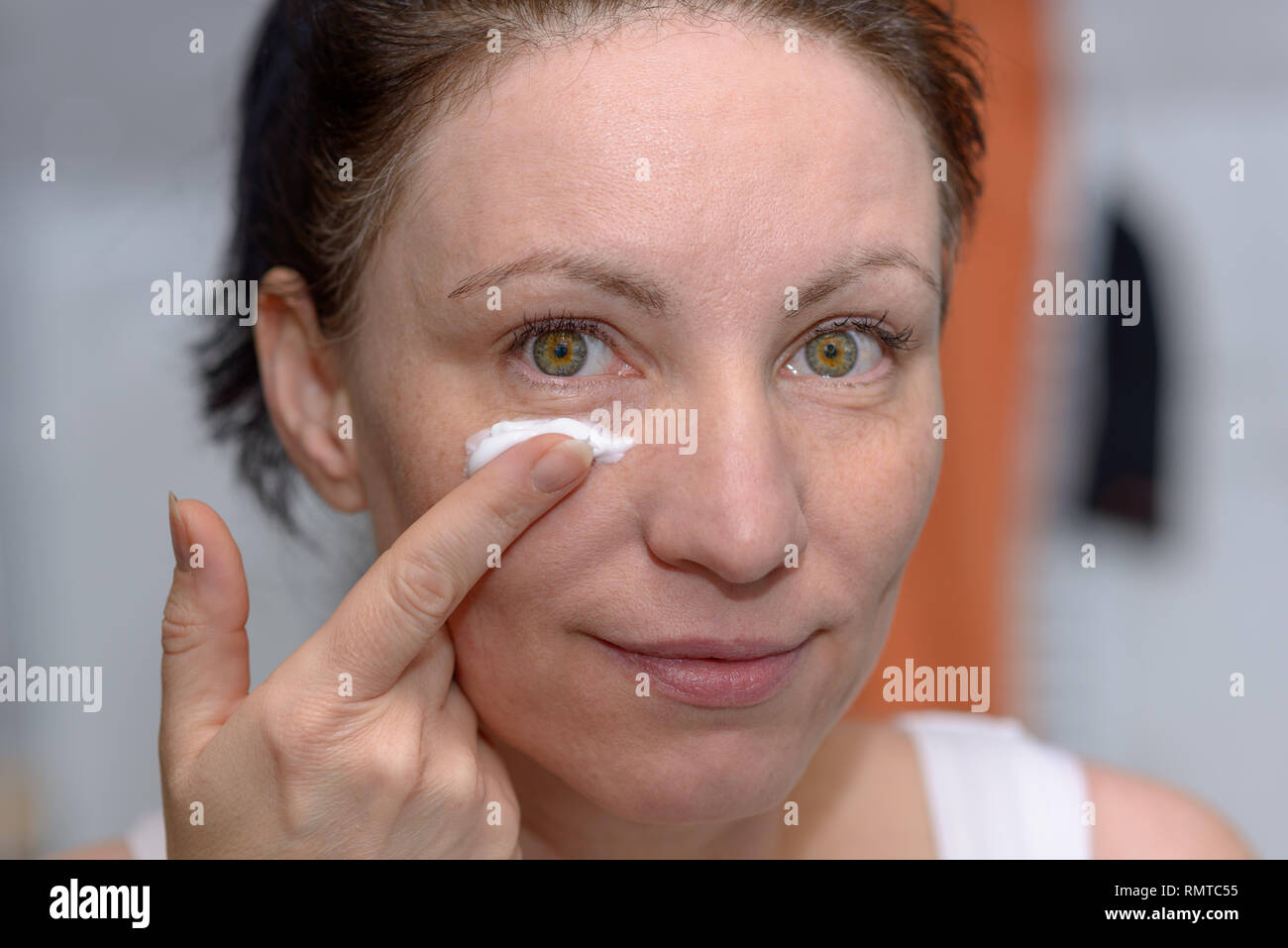 Woman holding a blob of moisturising cream on the tip of her finger in front of her face in a skincare and beauty concept - Stock Image
