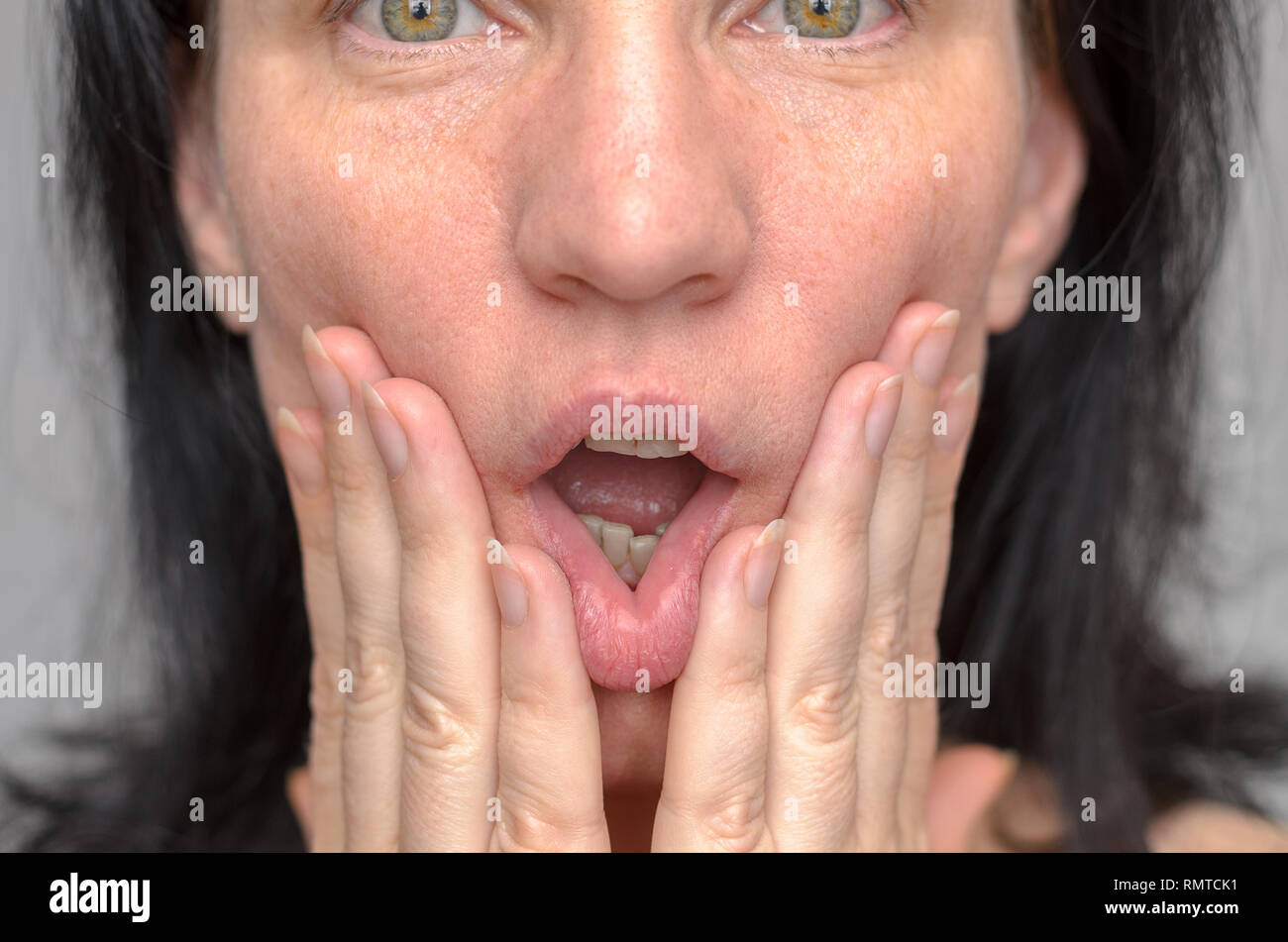 Woman with wide green eyes squashing her face with her hands holding her fingers to her cheeks on either side of her open mouth in a close up cropped  - Stock Image