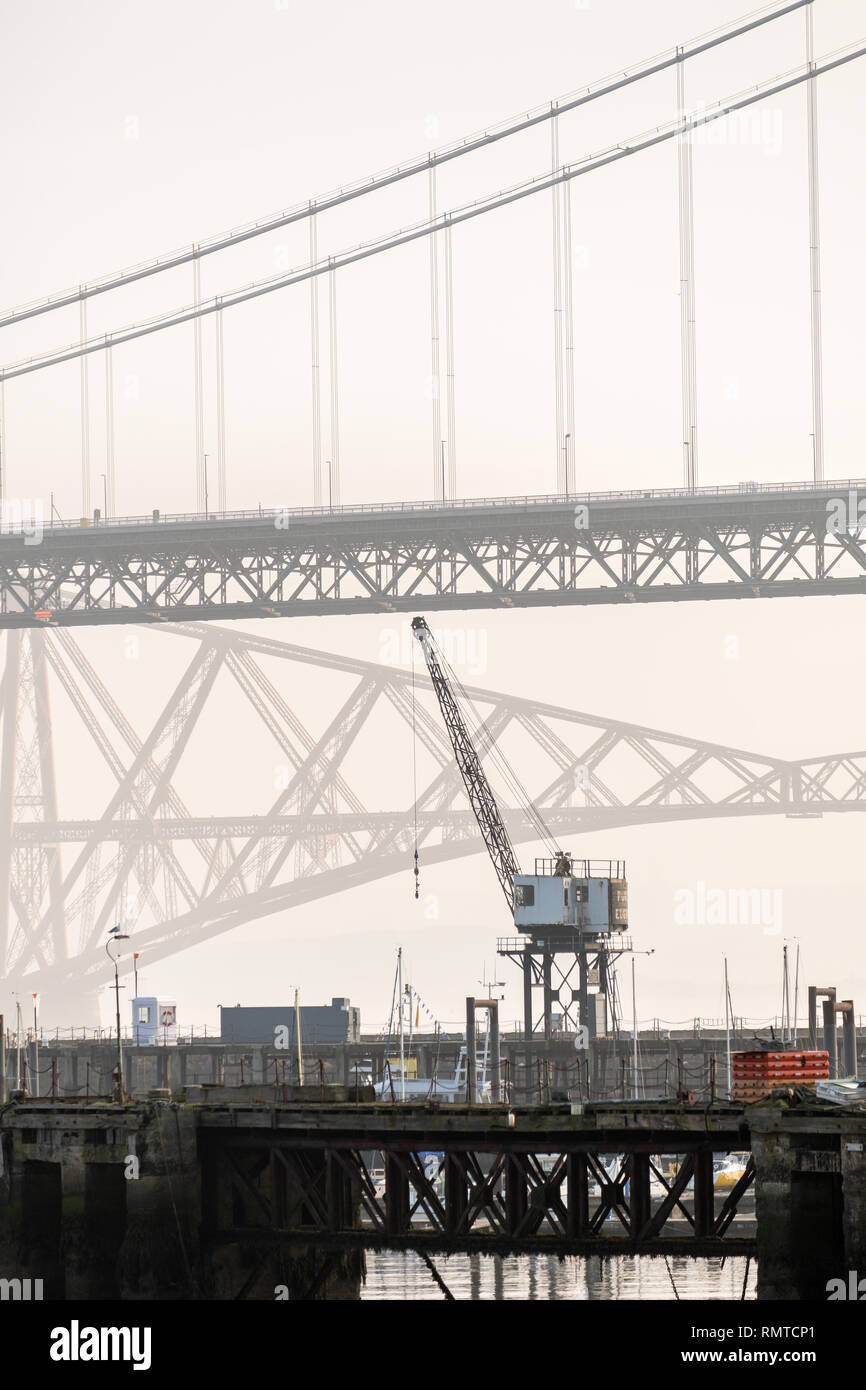 The old Forth Road bridge with a crane in the foreground, and the Forth Railway Bridge in the background on a misty day, Queensferry, Scotland Stock Photo