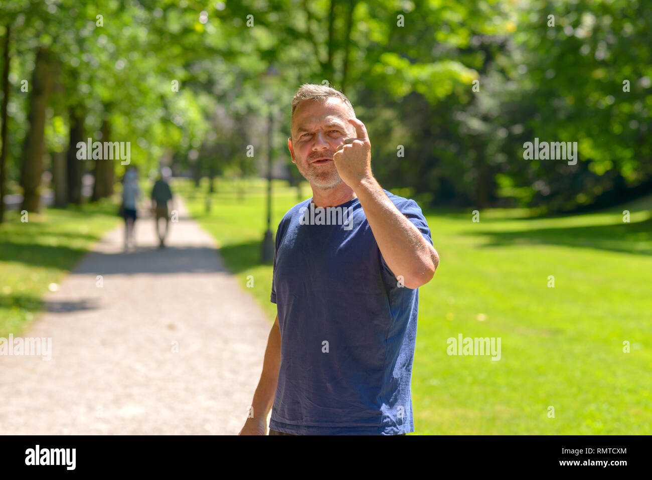 Fit middle aged man out jogging in a wooded green spring park pausing to turn and gesture with his finger at the camera - Stock Image