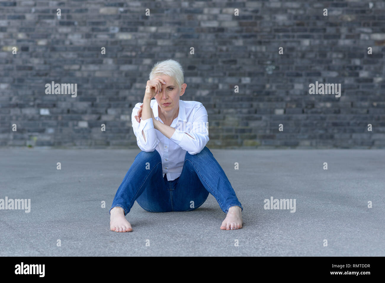 Depressed woman sitting on the ground before a black wall - Stock Image