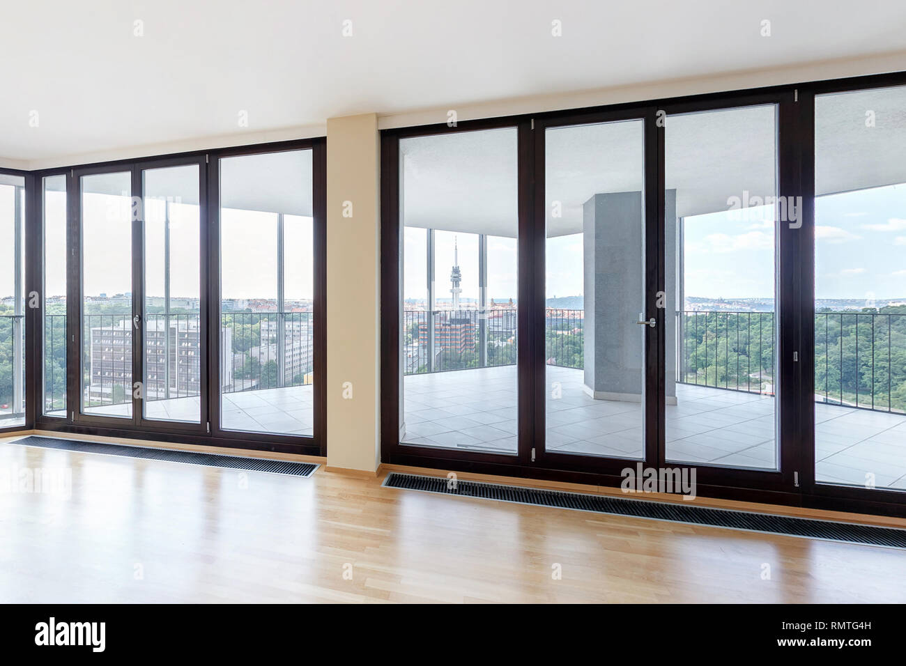 Modern white empty loft apartment interior with parquet floor and panoramic windows, Overlooking the metropolis city Stock Photo