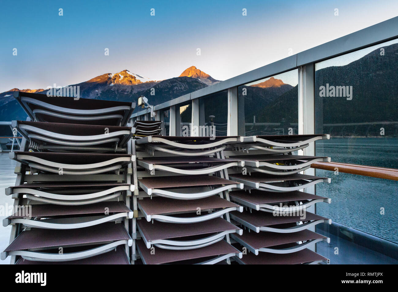 Stacked and secured lounge chairs on cruise ship outdoor deck with early morning sunrise light on mountainous background, near Skagway, Alaska, USA. - Stock Image