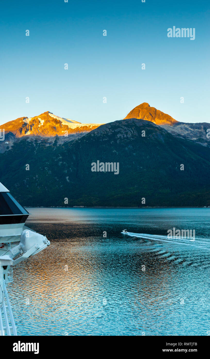 Taiya Inlet, sunlit mountains and small boat at dawn on calm early morning from deck of cruise ship, Skagway, Alaska. - Stock Image