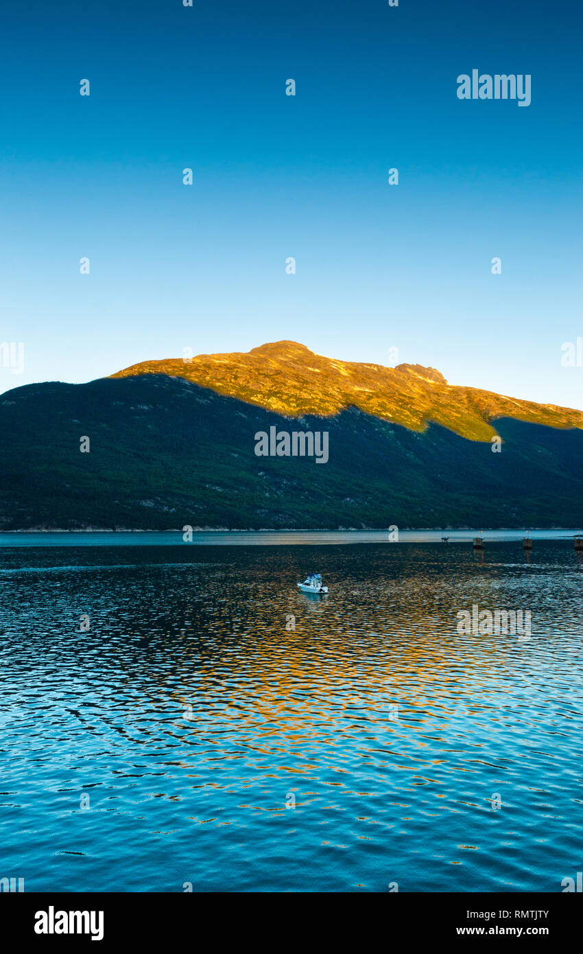 Small boat and sunrise light on mountains at dawn on calm early morning in beautiful Taiya Inlet, Skagway, Alaska. - Stock Image