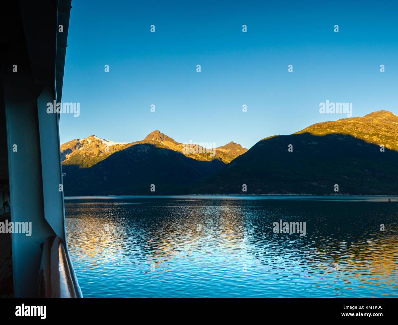 Early morning sunrise light on mountains, from outdoor promenade deck of cruise ship, Taiya Inlet, Skagway, Alaska, USA. - Stock Image