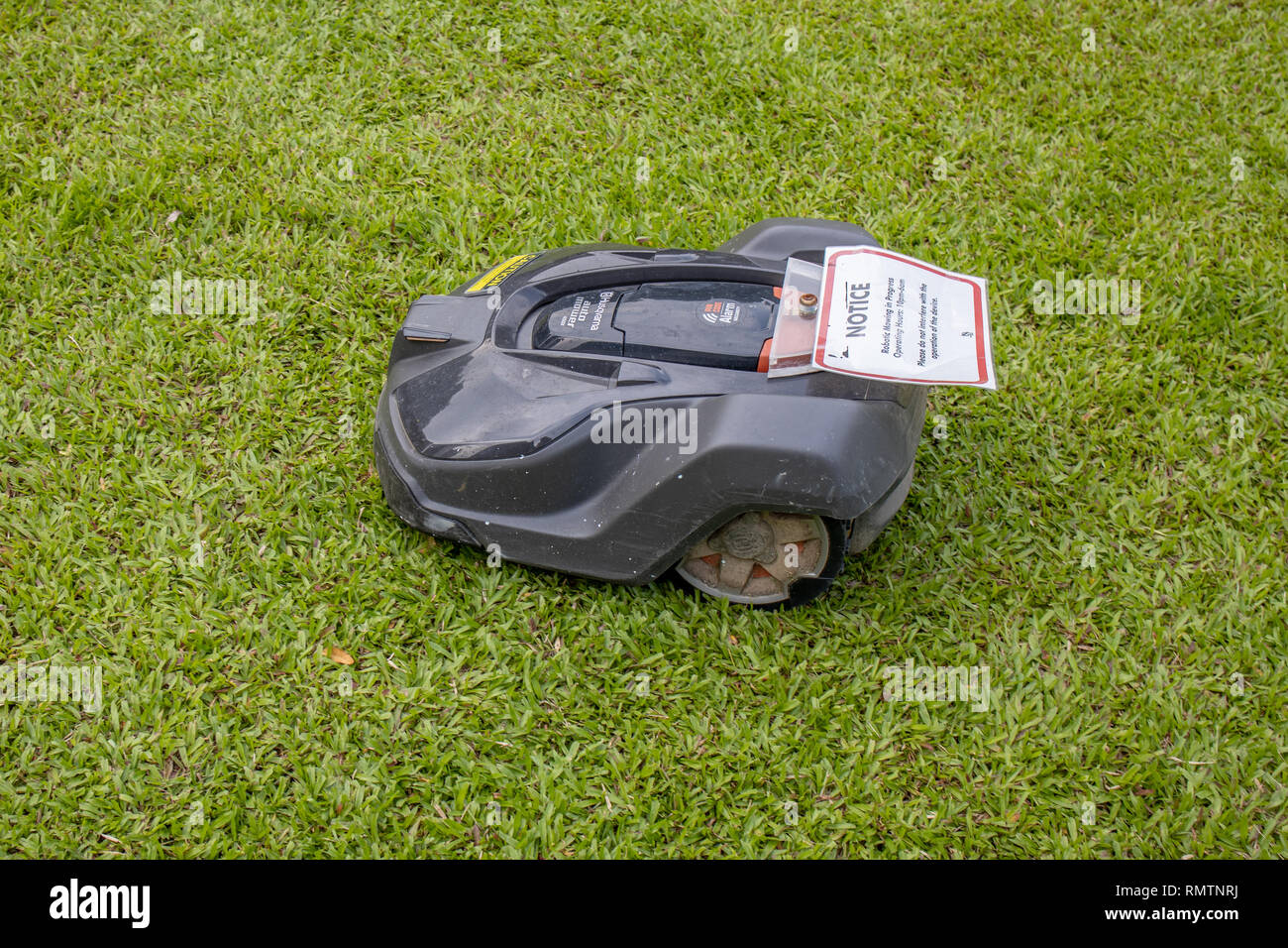 husqvarna robot lawn mower in a public park in Singapore - Stock Image