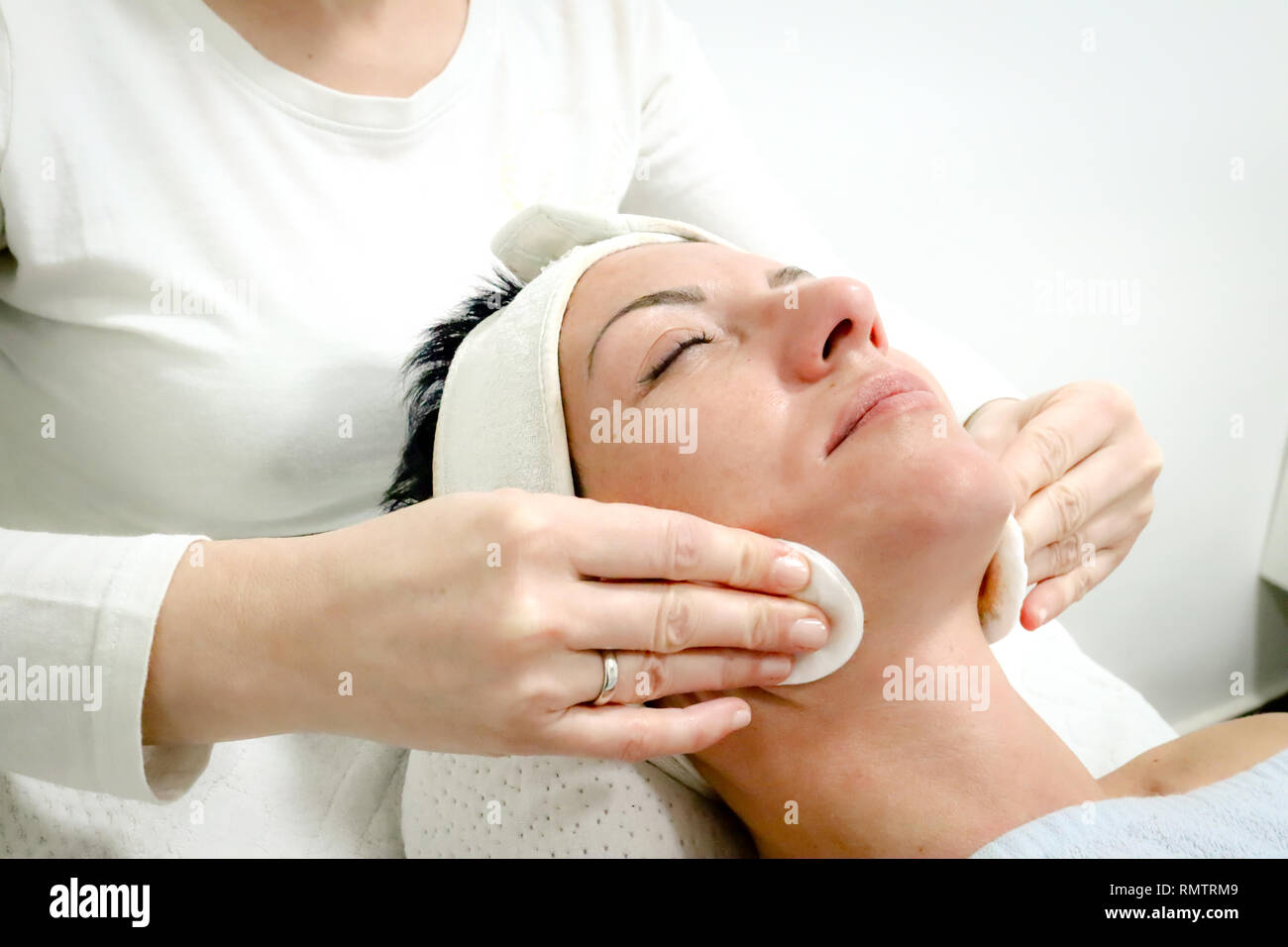beautician worker gently massages face of female costumer in beauty salon - Stock Image