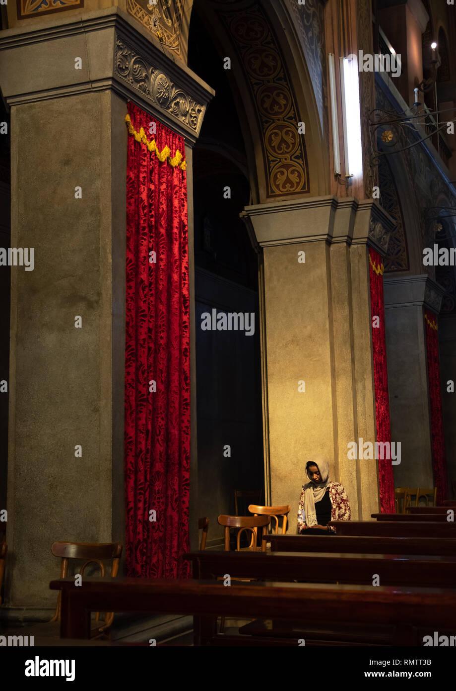 Woman praying inside st Matthew cathedral, Khartoum State, Khartoum, Sudan - Stock Image