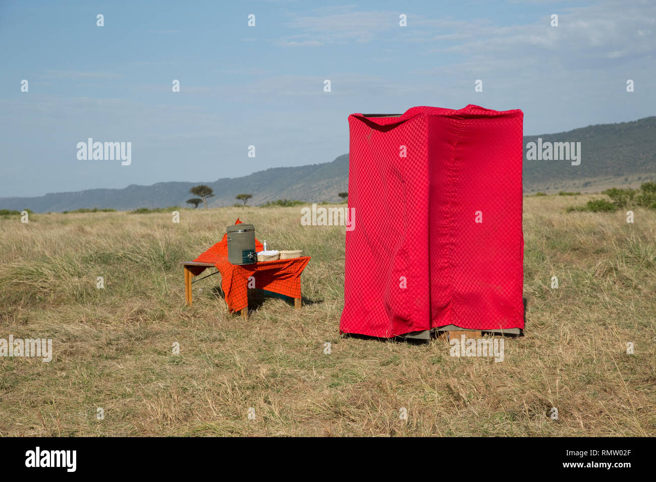 Red loo with a view, erected for breakfast after balloon flights on grassland plains, Masai Mara, Kenya - Stock Image