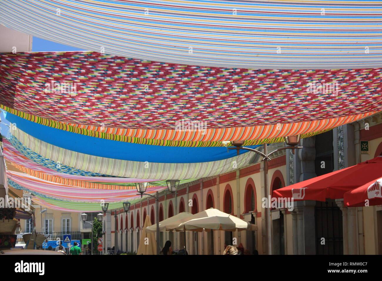 Aufgehangene farbige Tücher als Sonnenschutz und Dekoration - Stock Image