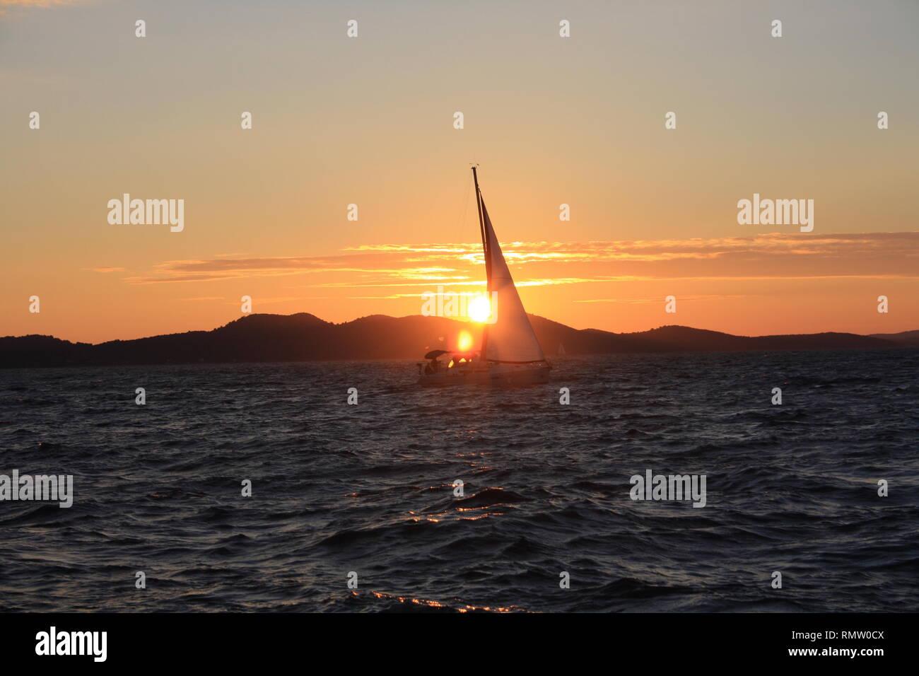 Sonnenuntergang mit Segelboot auf dem Wasser und Bergen im Hintergrund - Stock Image