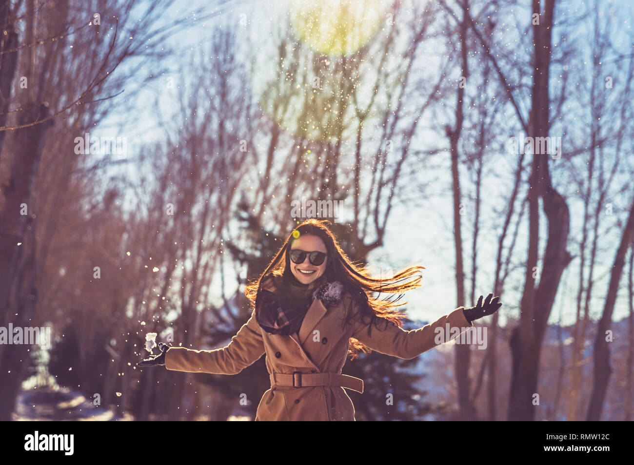 4b6d1a3de17 Portrait of a pretty girl wearing sunglasses and with pleasure spending  time in bright sunny day in winter park
