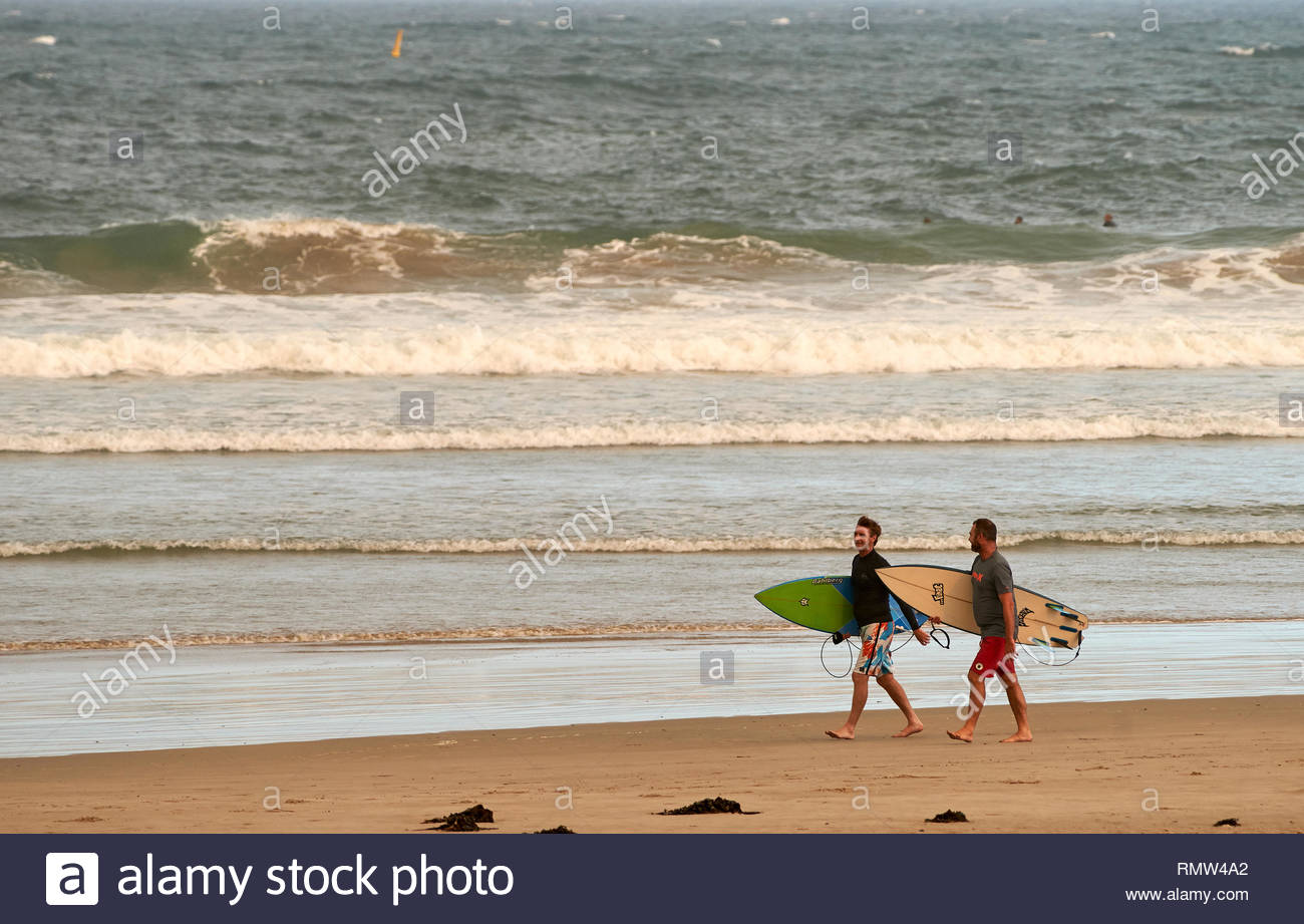 Two middle-aged male surfers in wet-suits, carrying their surfboards and conversing; walking along the beach beside the sea. Turners Beach, Australia. - Stock Image