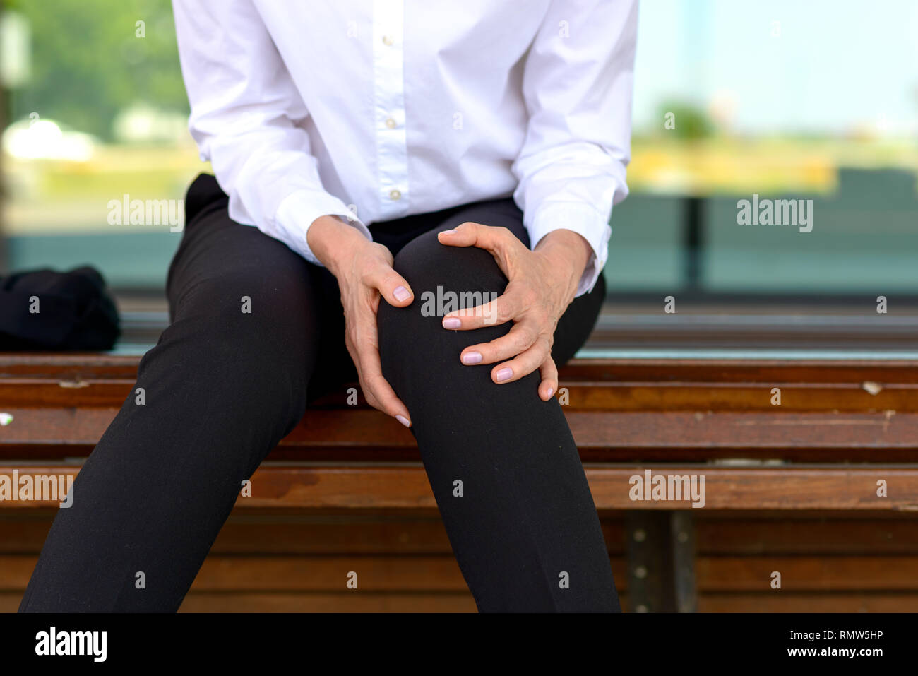 Businesswoman is holding her aching knee while sitting on a bench - Stock Image