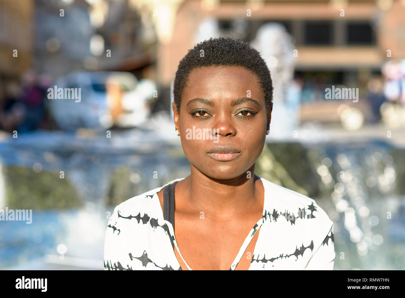 Stylish young African woman with a calm deadpan expression staring quietly at the camera standing in front of a city fountain - Stock Image