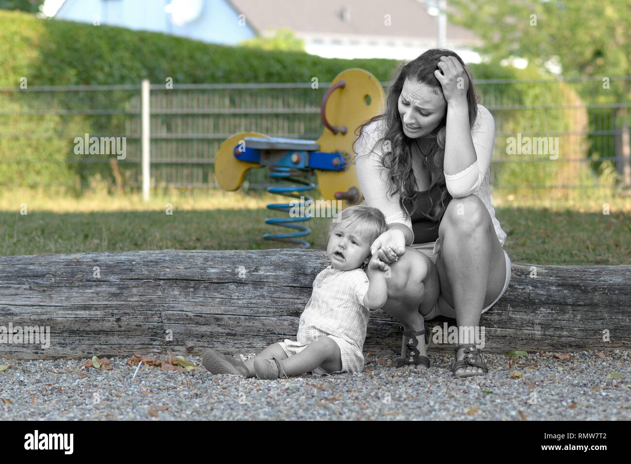 Troubled stressed young mother with her crying unhappy baby son outdoors in a playground in a conceptual image with de-saturated foreground - Stock Image