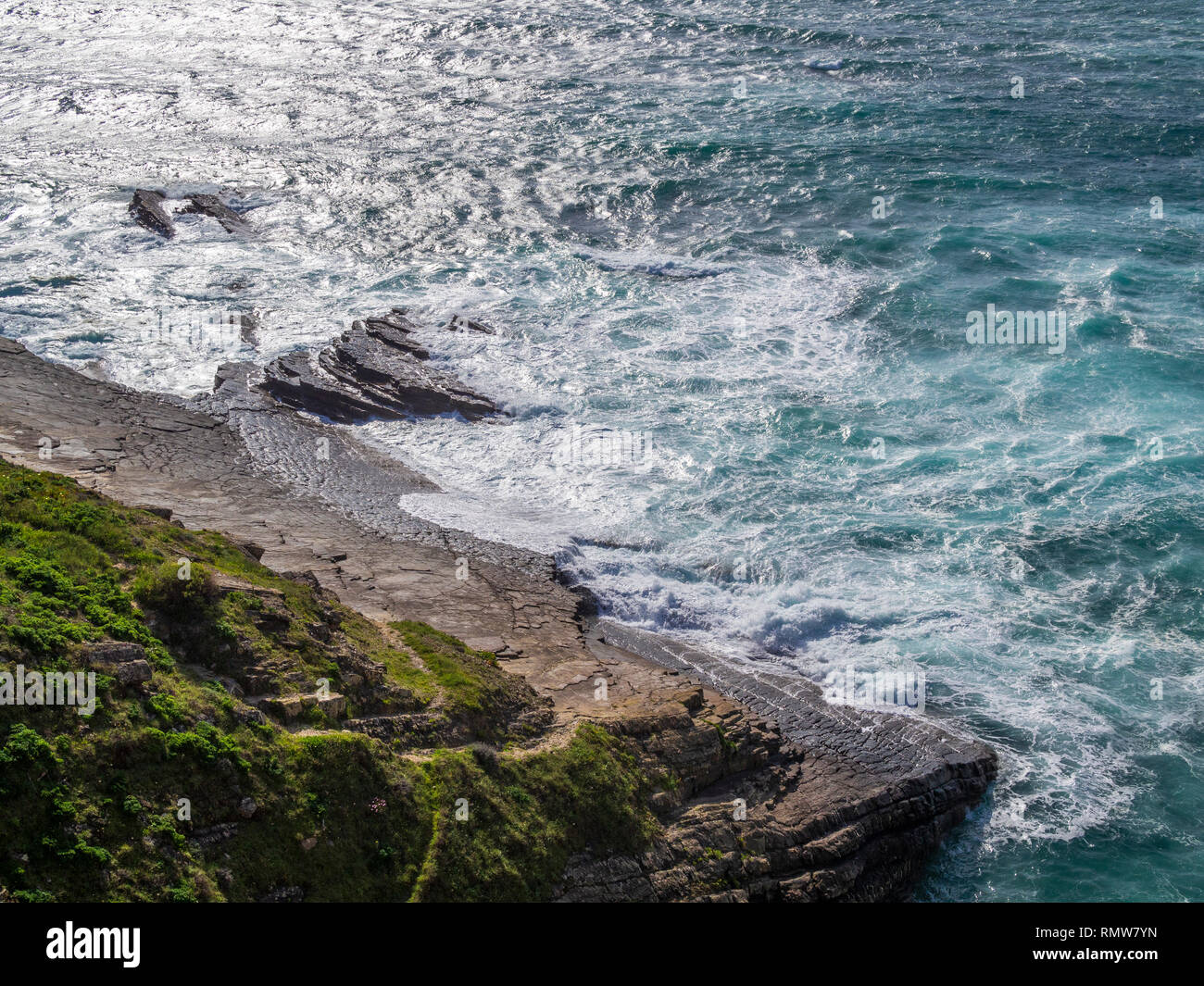 Rock ledges plunging onto the sea at Zambujeira do Mar, a village on the western coast of southern Portugal. - Stock Image