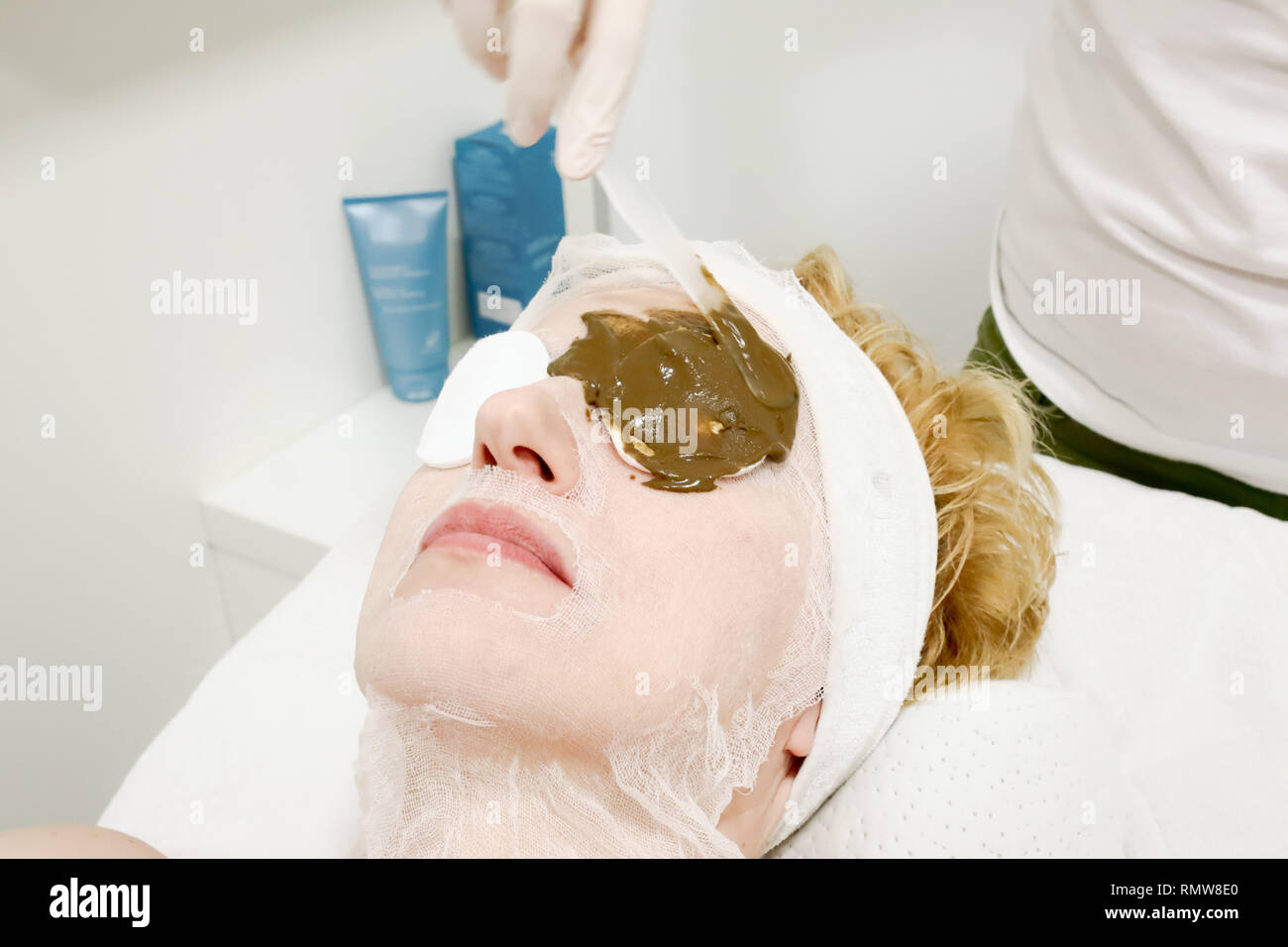 beautician worker applying  cosmetic facial mask of sea algae for anti aging and  hydration of skin  to female client in beauty salon - Stock Image