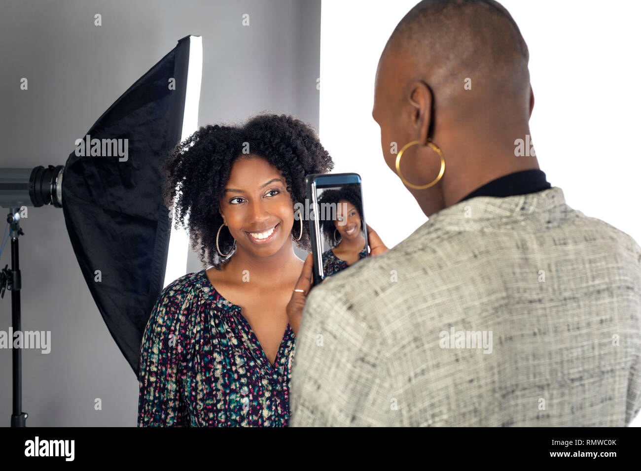 Black female actress doing a self tape audition via cell phone camera in a  studio while