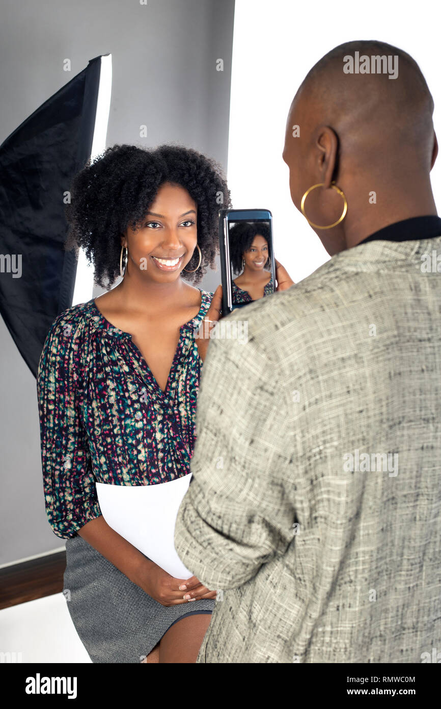 Black female actress doing a self tape audition via cell phone camera in a studio while reading to a casting director.  Depicts the Hollywood industry - Stock Image