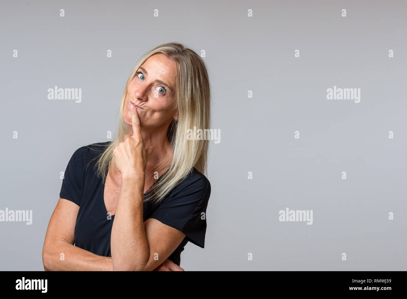 Speculative woman looking at the camera with wide eyed thoughtful expression with her head tilted to the side and hand to her chin over grey with copy - Stock Image