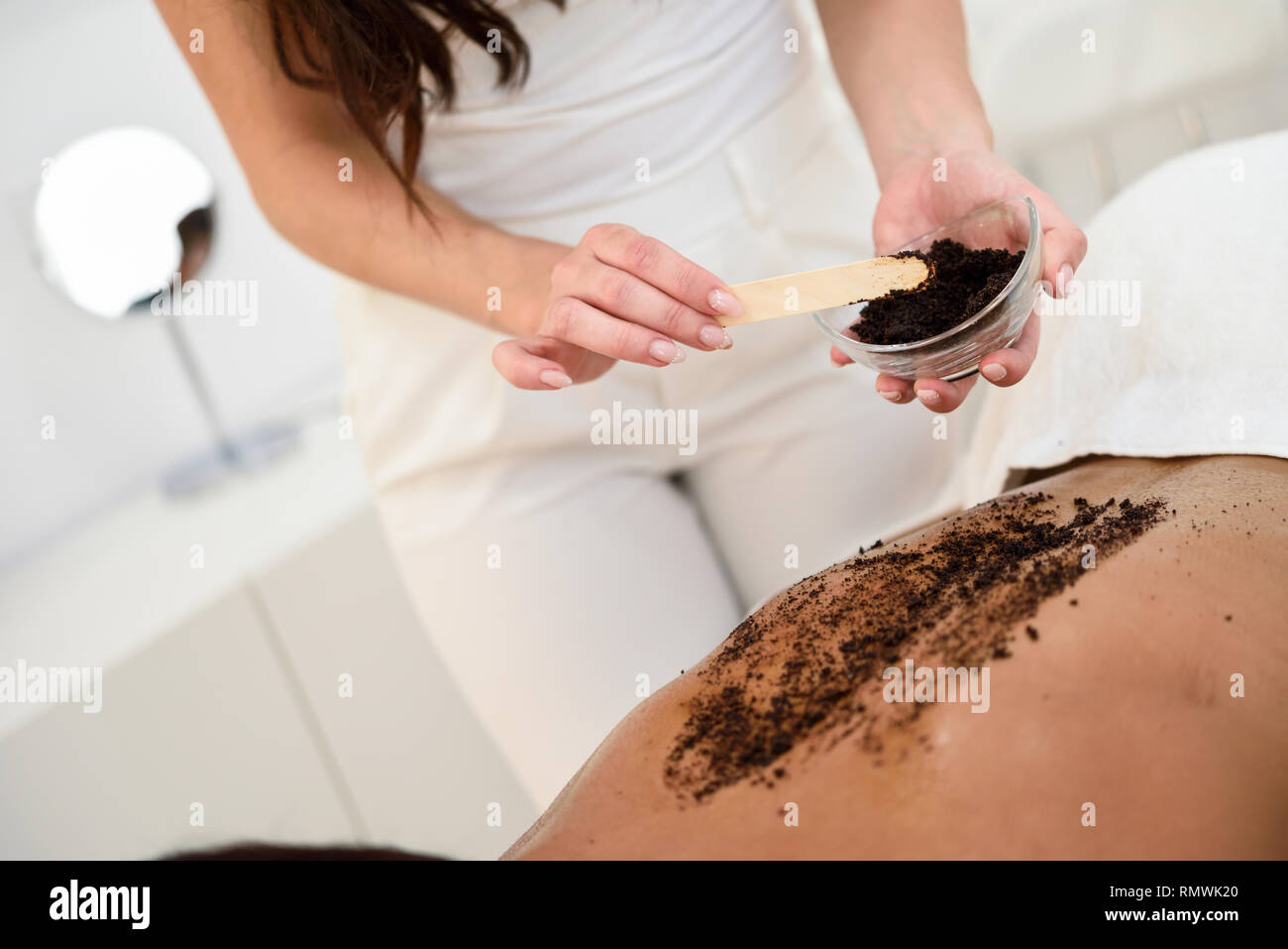 Woman cleans skin of the body with coffee scrub in spa wellness center.  - Stock Image