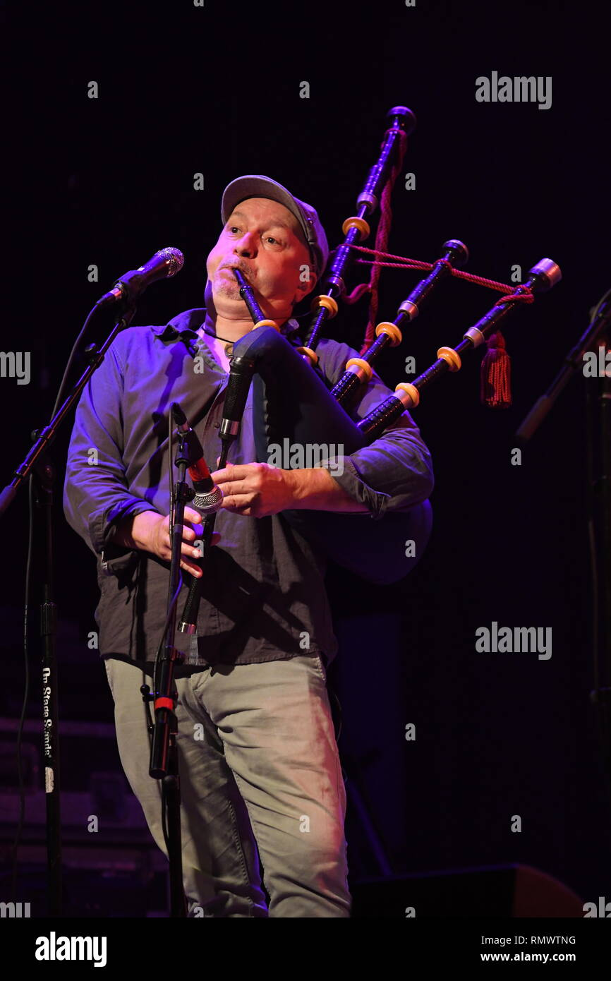 Enter the Haggis band member Craig Downie is shown performing on stage during a 'live' concert appearance. - Stock Image