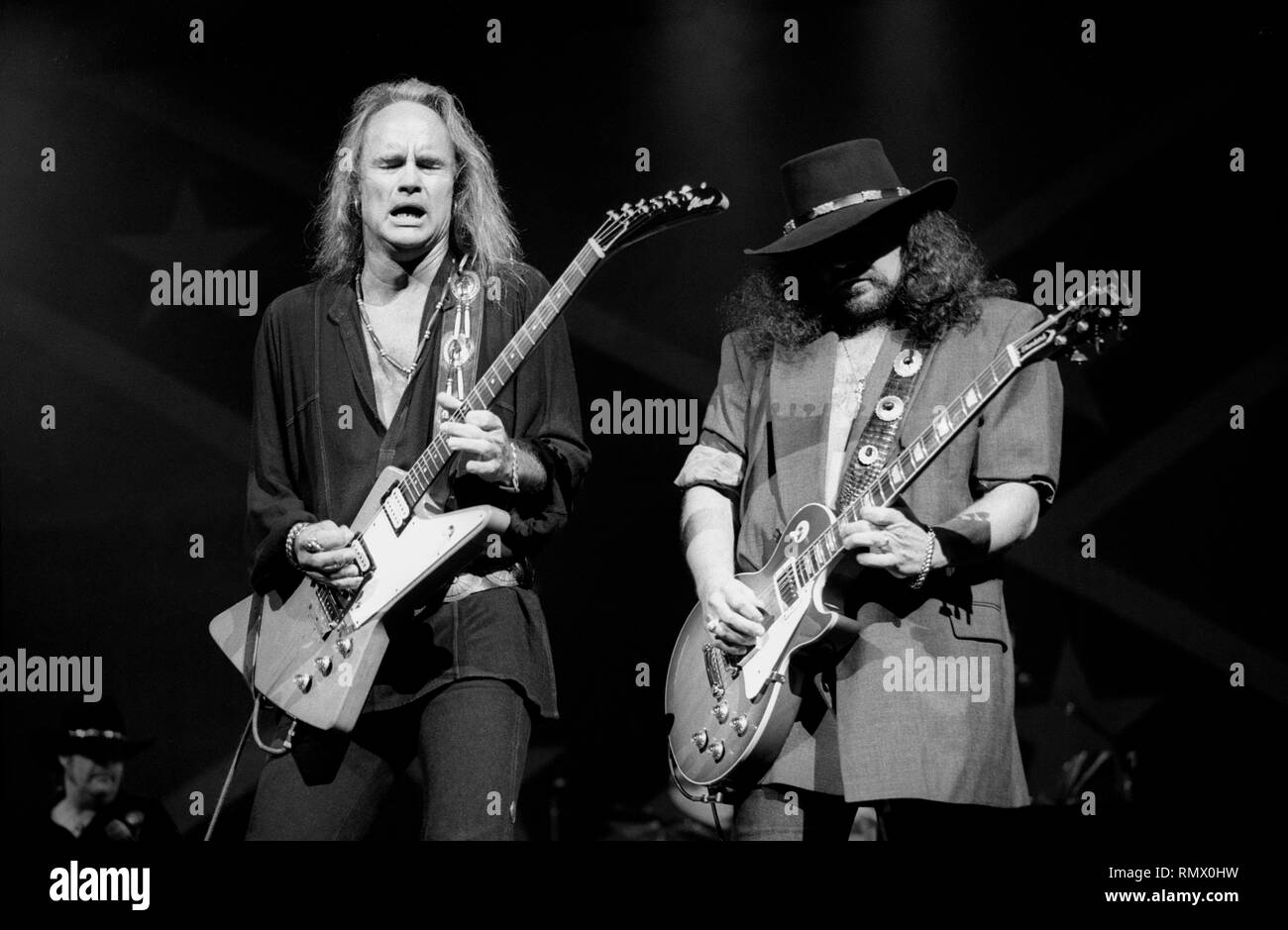 """Guitarists Rickey Medlocke and Gary Rossington are shown performing on stage during a """"live"""" concert appearance with the Lynyrd Skynyrd. Stock Photo"""