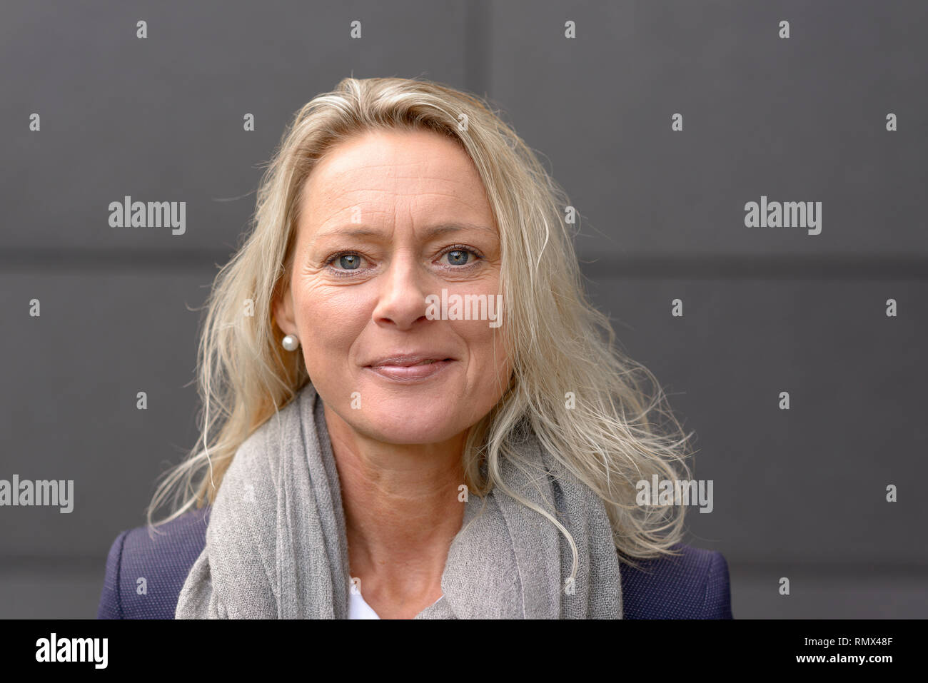 Mature attractive grey woman with tousled shoulder length hair looking friendly at the camera with a quiet smile in front of a grey wall - Stock Image