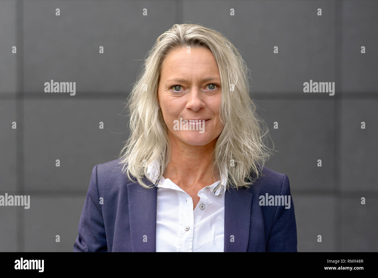 Mature attractive grey woman with tousled shoulder length hair looking intently at the camera with a quiet smile in front of a grey wall - Stock Image