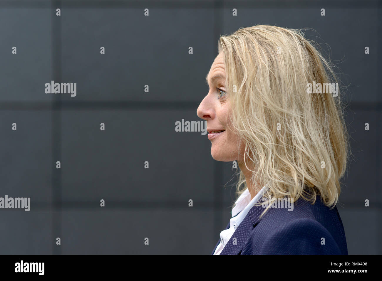 Profile head shot of a surprised blond woman with tousled hair smiling and raising her eyebrows with copy space on a dark grey wall - Stock Image