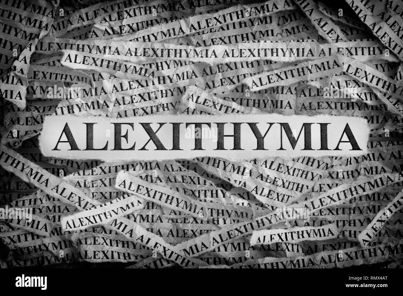 Alexithymia. Torn pieces of paper with the words Alexithymia. Concept image. Black and White. Close up. - Stock Image