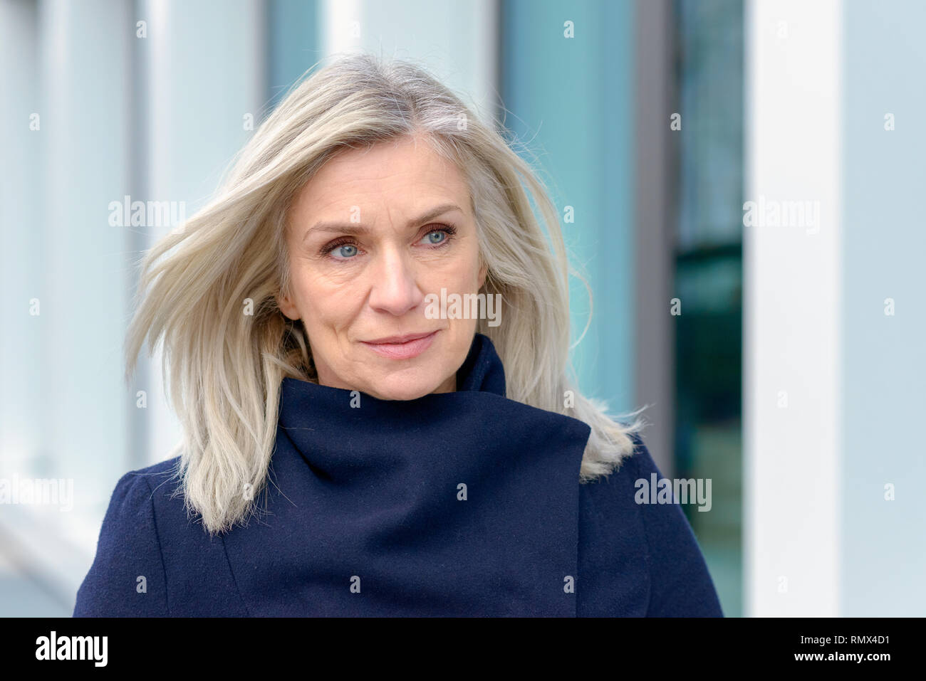 Attractive blond woman with a warm happy smile dressed in a warm winter overcoat standing outdoors smiling at the camera - Stock Image