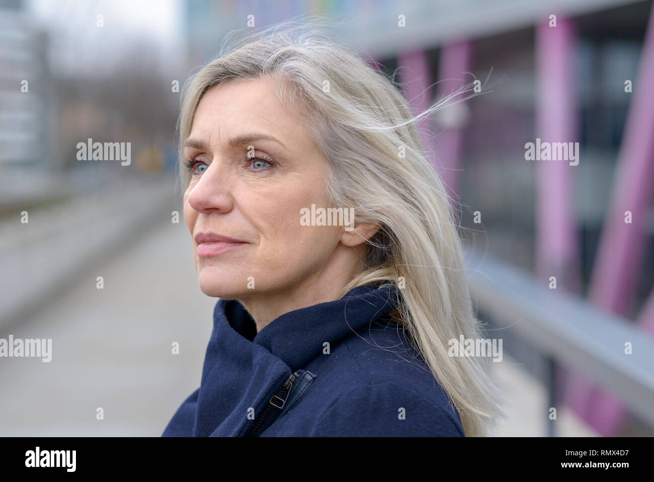 Serious woman looking intently to the side with a thoughtful expression as she stands outdoors in town on a walkway Stock Photo