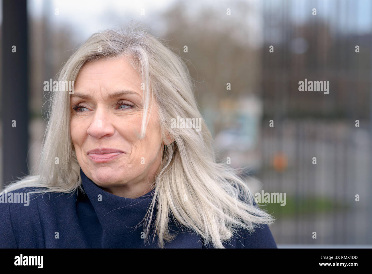 Attractive mature woman with tousled shoulder length blond hair looking to the left of the frame with a pleased smile against a blurred urban backgrou - Stock Image