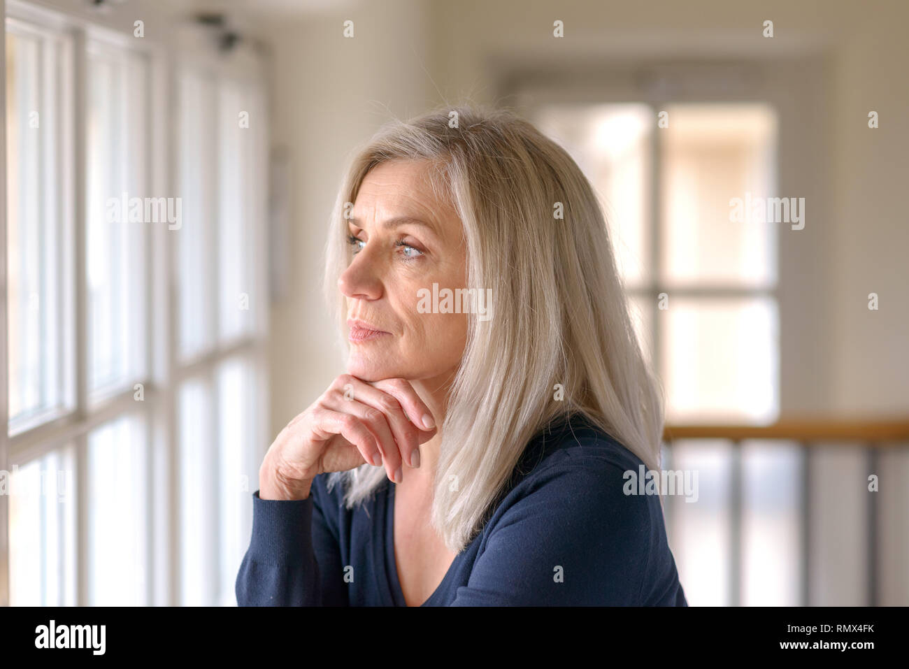 Attractive thoughtful woman with serious expression standing with her hand to her chin staring quietly out of a large window Stock Photo
