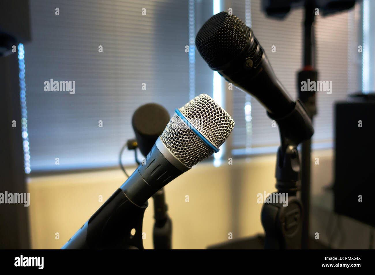 Microphones on stands in a rehearsal room - Stock Image