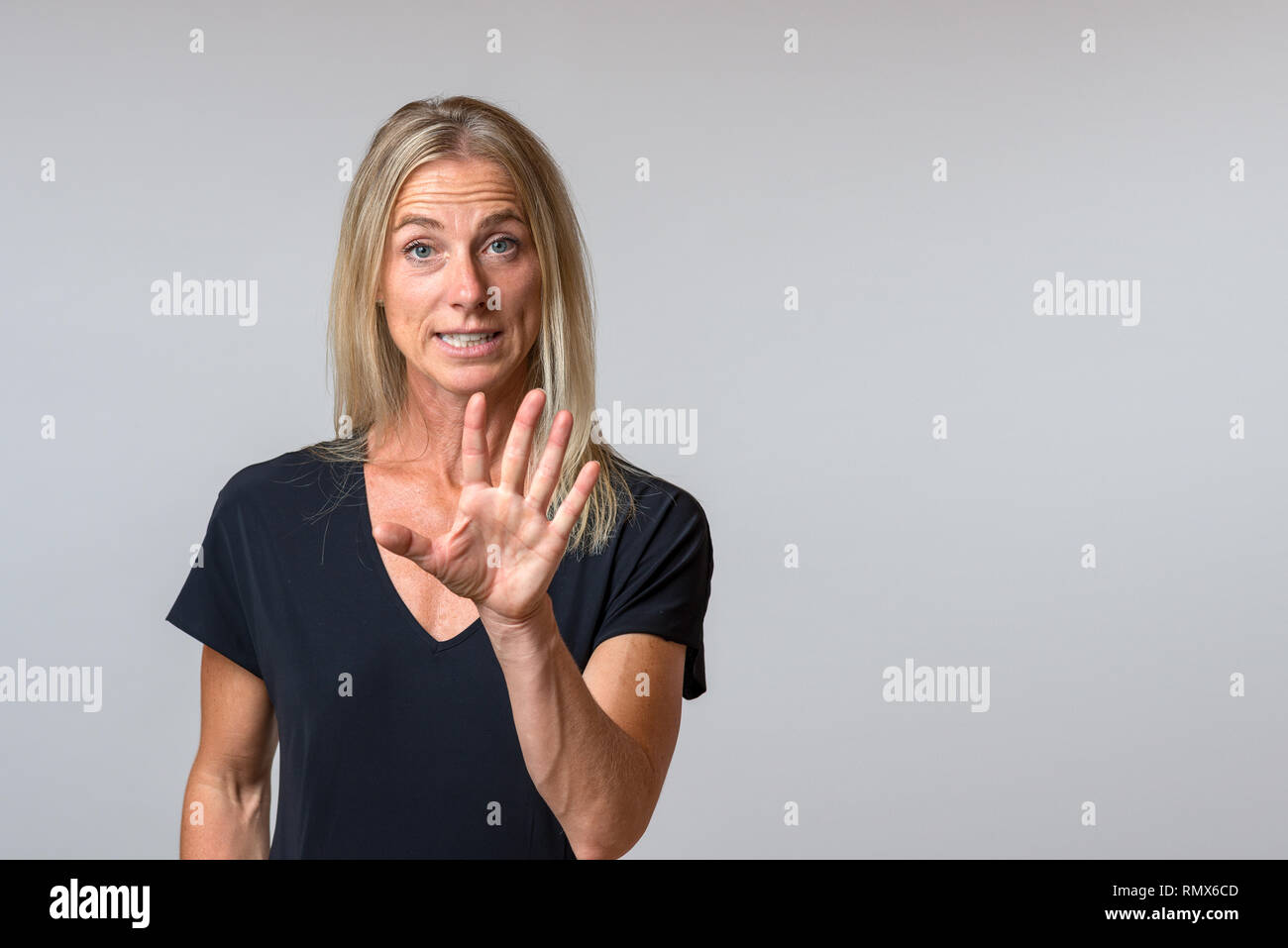 Persuasive vociferous woman speaking and gesturing with her hand in emphasis as she makes a point isolated on grey with copy space - Stock Image
