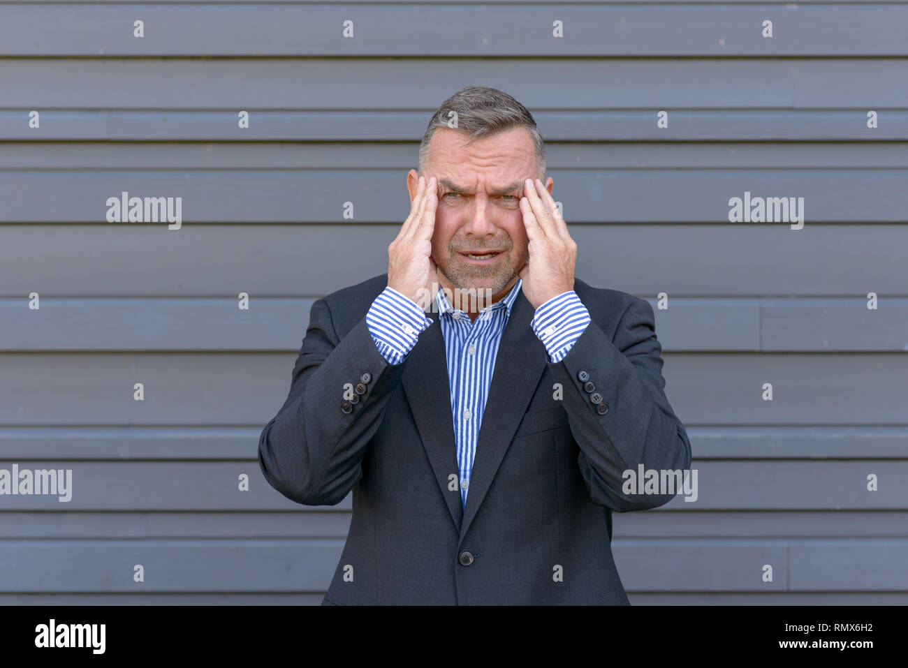 Stressed businessman, or suffering from a headache, standing with his hands to his temples grimacing against a grey exterior wall - Stock Image