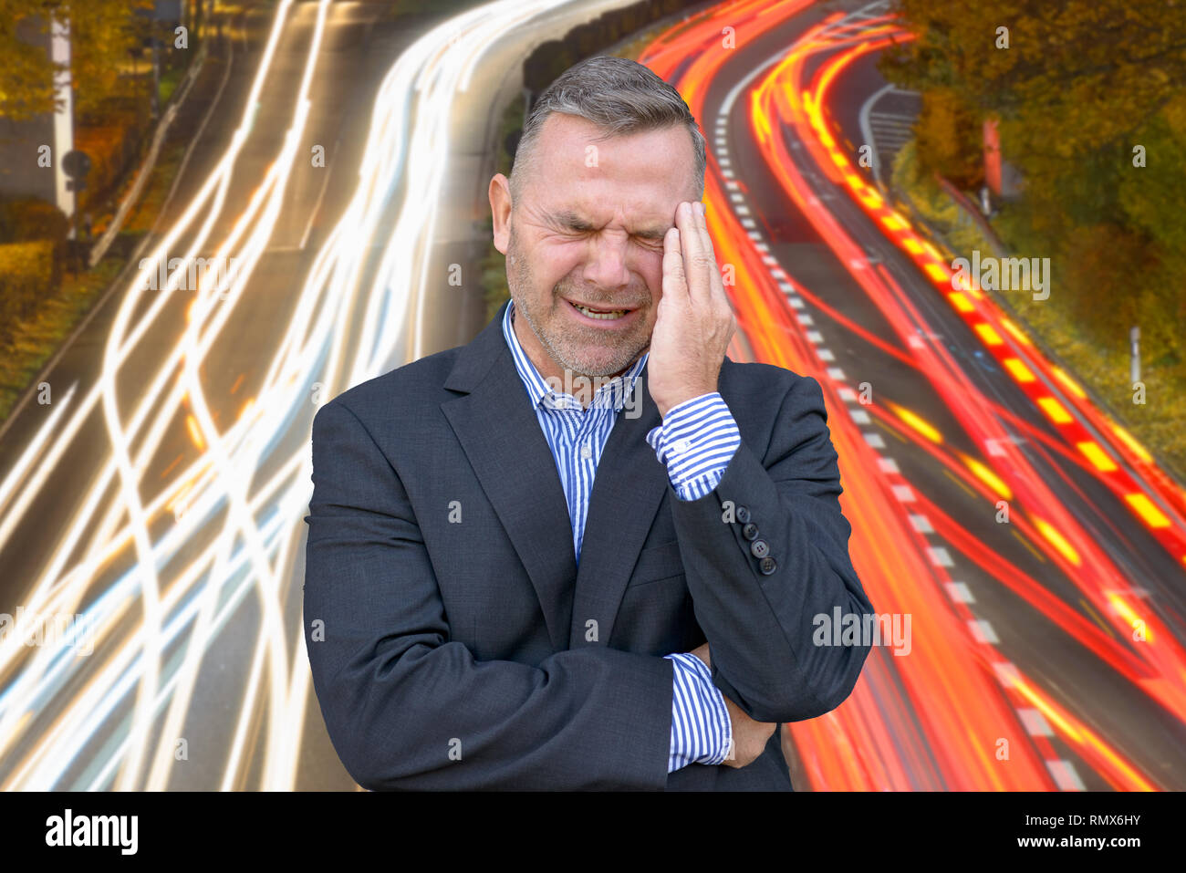 Stressed businessman, or suffering from a headache, standing with his hand to his temple grimacing against Long exposure light trails of traffic on a  - Stock Image