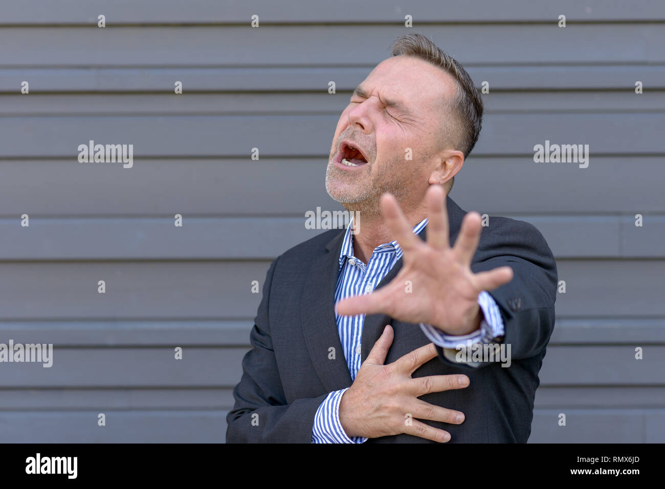 Businessman clutching his chest in pain or anguish while reaching out with his other hand in desperation against a grey wall with copy space - Stock Image