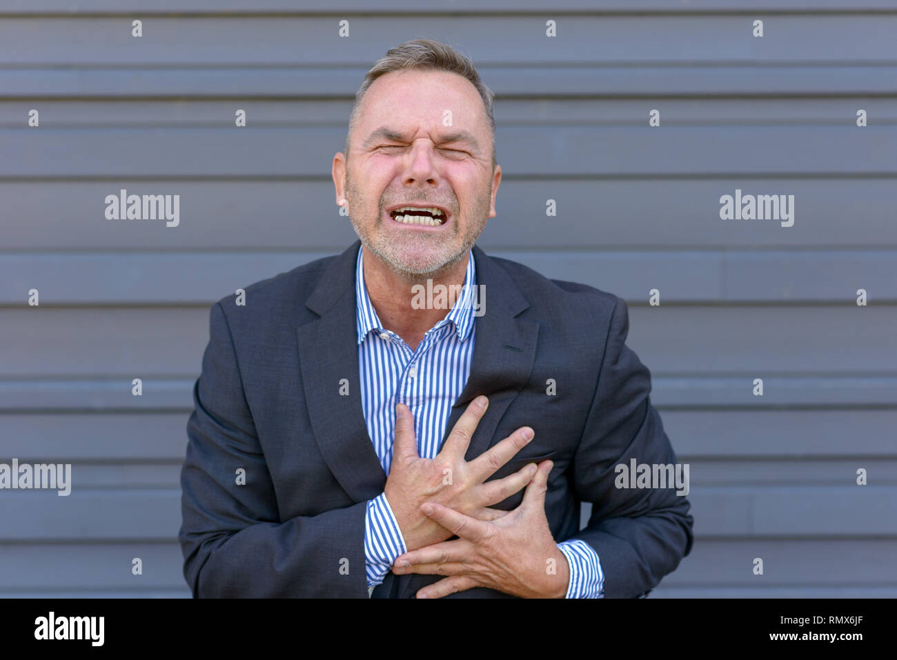 Middle-aged businessman suffering chest pains clutching his chest and grimacing as a prelude to a heart attack or myocardial infarct - Stock Image