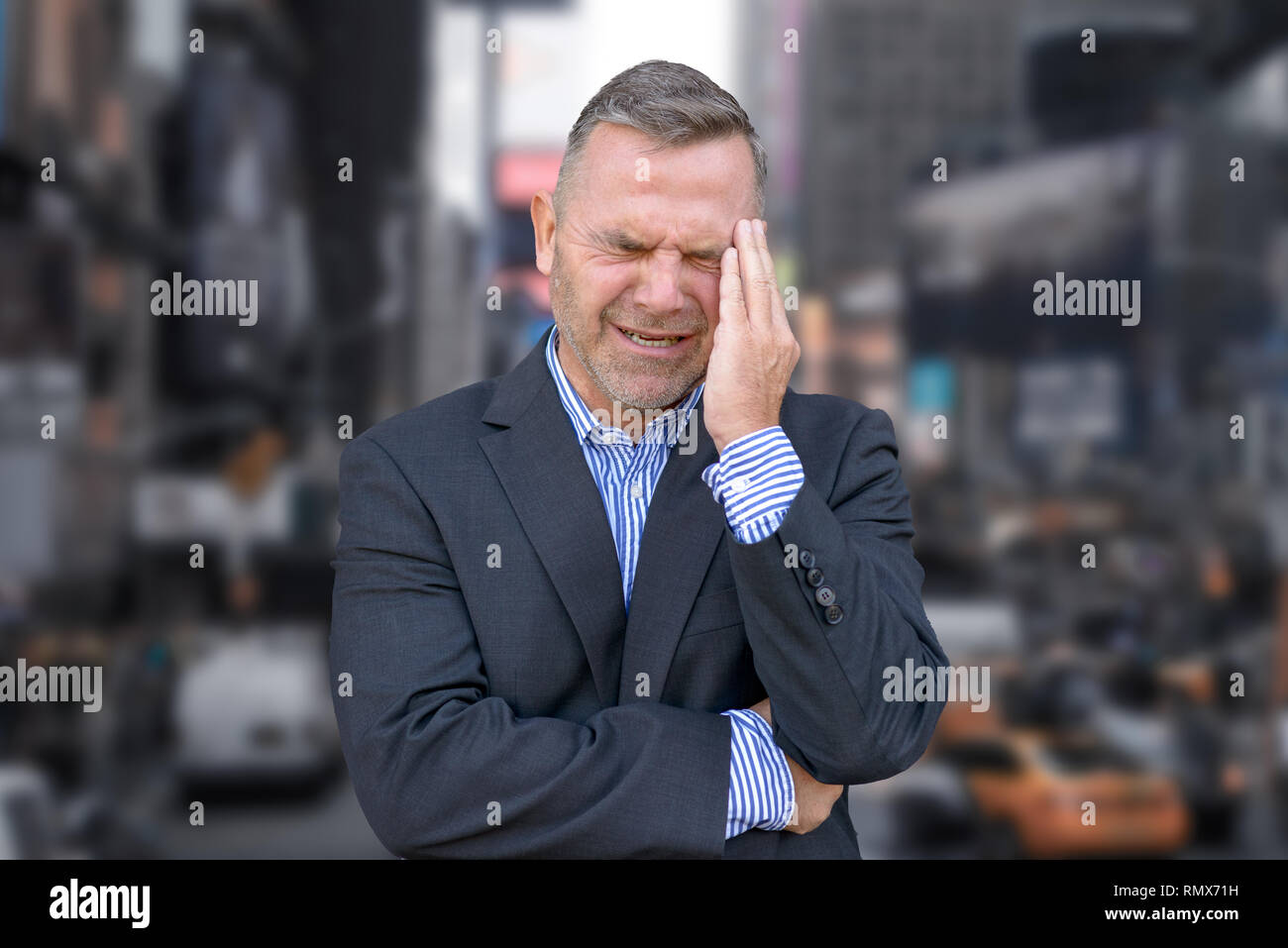 Stressed businessman, or suffering from a headache, standing with his hand to his temple grimacing against downtown of a big city - Stock Image